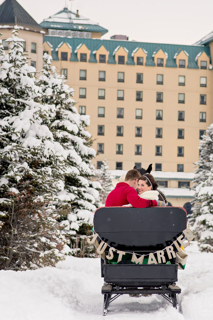 couple on fairytale sleigh ride after wedding - Photo Credit: Orange Girl Photography