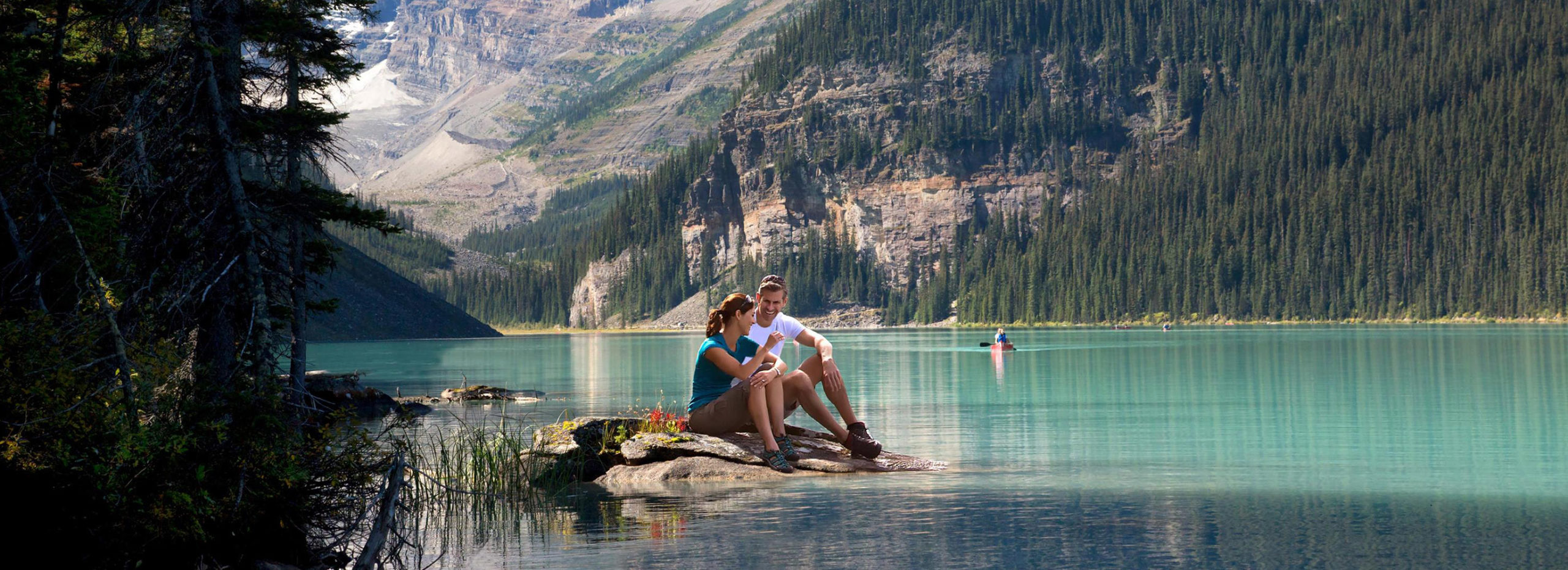 couple sitting together at lake louise shore