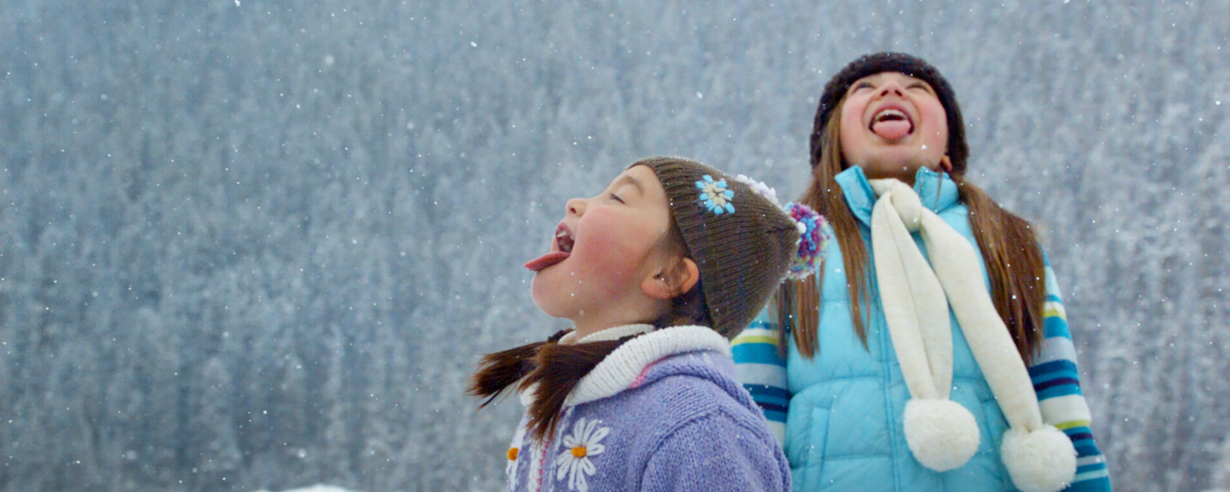 Two girls standing in the falling snow