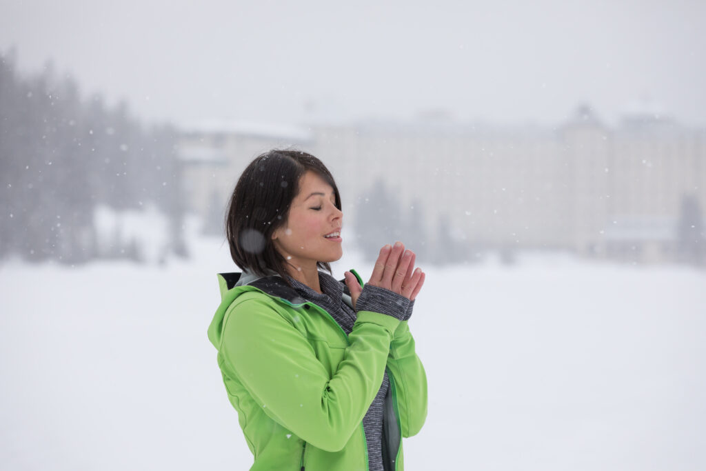 Woman meditating outside in the snow